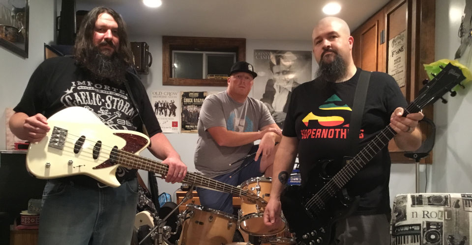 Colorful photo of rock group Nostalgic Distortion posing with instruments in practice space.
