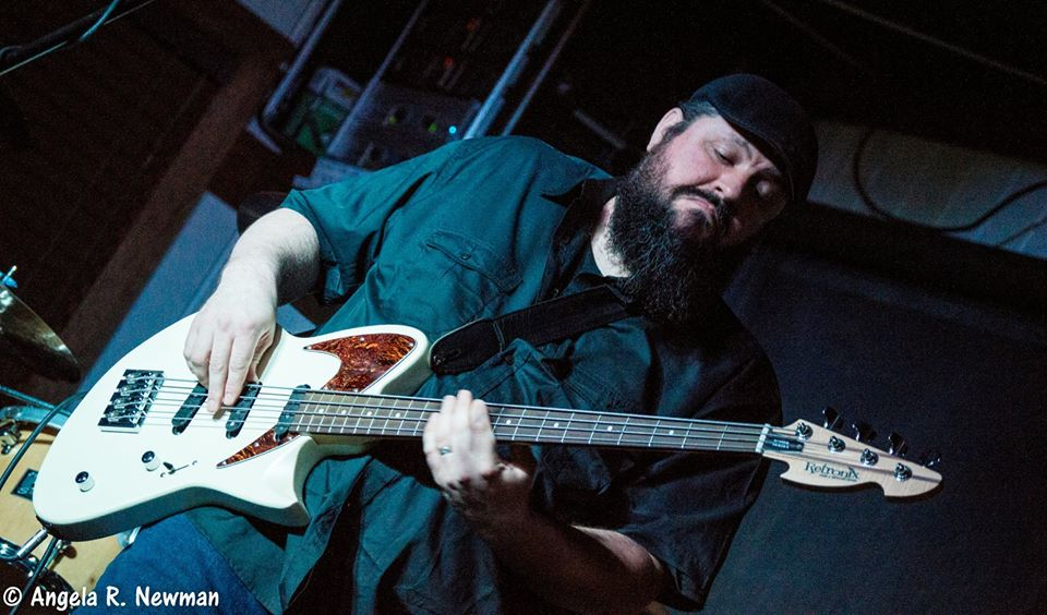 Photo of Ryan Byrne in black collared shirt and black flat cap playing white Retronix bass guitar live on stage.
